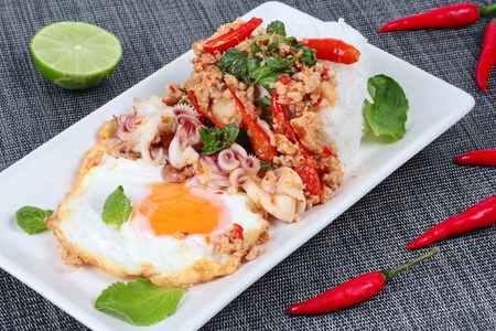 stirred: Rice topped with stirred  minced-pork ,squid ,basil and fried egg(sunny up) on black napery.