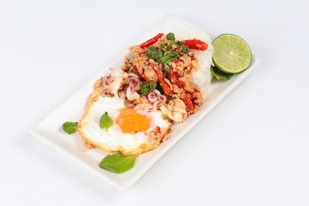 stirred: Rice topped with stirred  minced-pork ,squid ,basil and fried egg(sunny up) on white background. Stock Photo