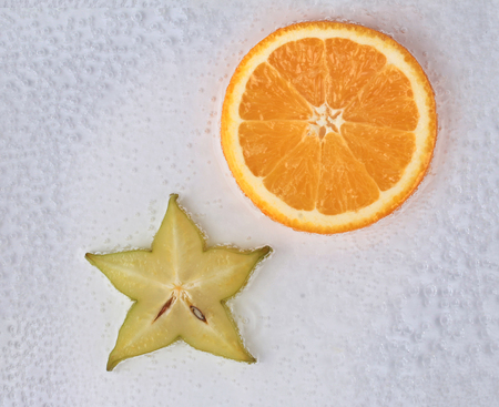 Sun and Star ,Sliced halves of star apple and orange on air bubble in water.