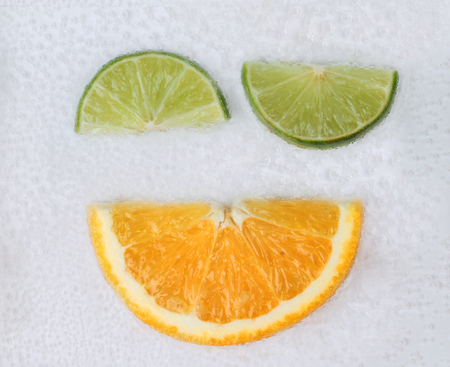 Emotion Wink ,Sliced halves of green lemons and orange on air bubble in water.