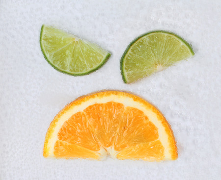 Emotion Annoyed ,angry ,Sliced halves of green lemons and orange on air bubble in water.