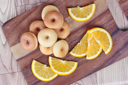 sliced orange: Milk donut with sliced orange home made on wood. Stock Photo