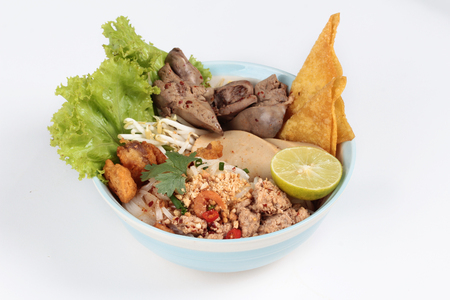 higado de pollo: Noodle with tom yam topped with minced pork,chicken liver,wonton,shrimp ,chili. and green lemon on white background. Foto de archivo