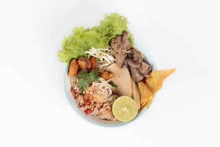chicken liver: Noodle with tom yam topped with minced pork,chicken liver,wonton,shrimp ,chili. and green lemon on white background. Foto de archivo
