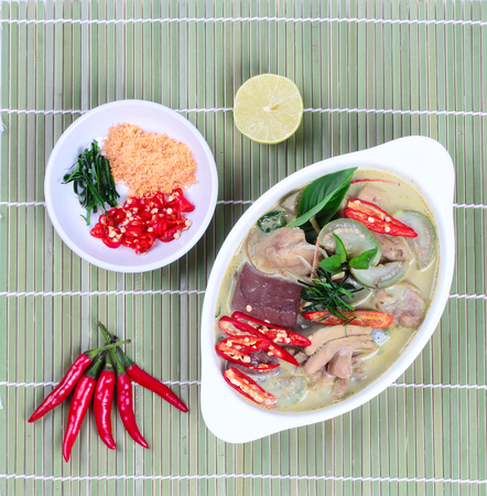 side dish: Green chicken curry in coconut milk served with side dish as minced dried shrimp,sliced red chili,sliced kaffir lime leaves and green lemon on bamboo. Stock Photo