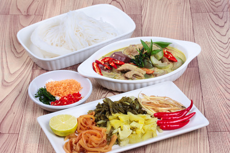side dish: Rice noodle and green chicken curry in coconut milk with side dish on wood.