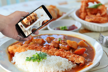 side dish: Using mobile phoe to take photo a food set of rice in yellow curry and side dish for share to social network. Selective focus. Stock Photo