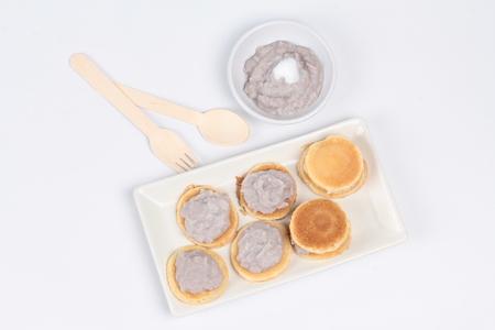 stirred: Mini pancake topped stirred taro on white background.