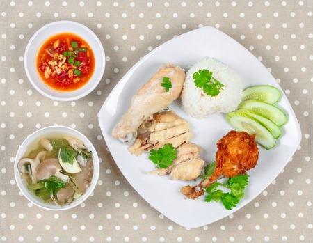 sesame street: Streamed oily rice and streamed chicken as Hainanese chicken rice and deep fried chicken served with chili in tofu sauce and mushroom soup on gray.