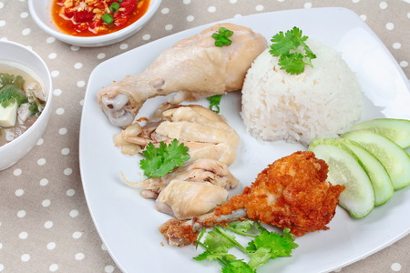 soy bean: Streamed oily rice and streamed chicken as Hainanese chicken rice and deep fried chicken served with spicy soy bean sauceand mushroom soup on gray.