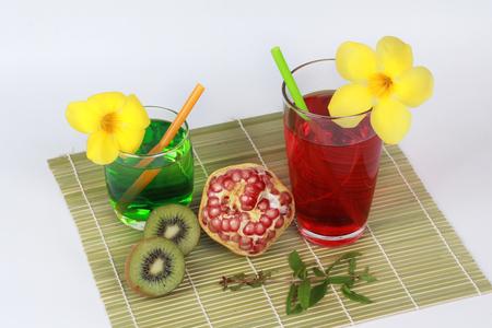 two tone: Pomegranate juice and two tone of kiwi juice  with peeled ripe  pomegranate and halves kiwi on bamboo.