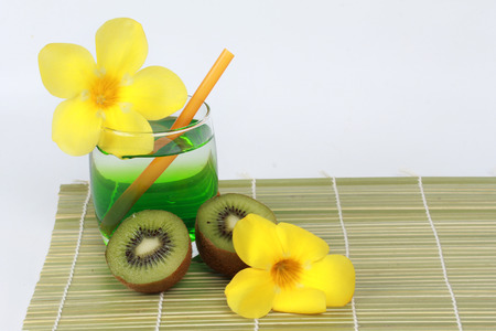 two tone: Two tone of kiwi juice served with halves kiwi and yellow flower on bamboo. Stock Photo