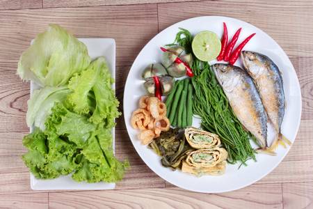 Ready side dish served as deep fired mackarelss,vegetable omelet,crispy pork rind,pickle lettuce,halve green lemon,red chili and boiled of eggplant,lentils,acacia on wood.Top view Stock Photo