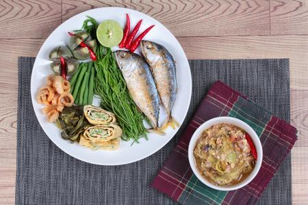 Green chili dip  Nam Prik Num and dish of deep fired mackarels,vegetable omelet,crispy pork rind,pickle lettuce,halve green lemon,red chili and boiled of eggplant,lentils,acacia on wood. Top view