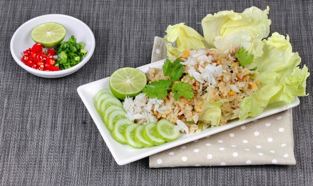 side dish: Fried rice with crab topped streamed crab,halve green lemon,sliced cucumber,lettuce and coriander served  spicy  sour filling side dish. Side view.