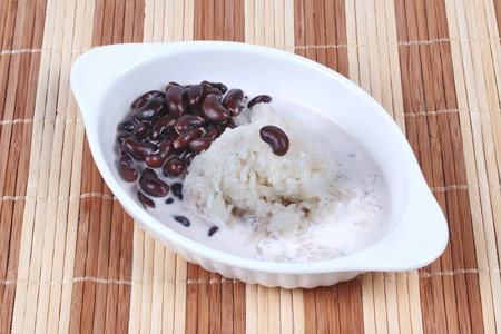 purine: Black bean and sticky rice in sweet coconut cream topped coconut milk on brown. Side view. Stock Photo