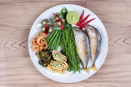 Ready side dish of deep fired mackarel,vegetable omelet,crispy pork rind,pickle lettuce,halve green lemon,red chili and boiled of eggplant,lentils,acacia  on wood.Top view