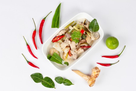higado de pollo: Chicken and galangal in coconut milk soup and herb on white background. Top view Foto de archivo