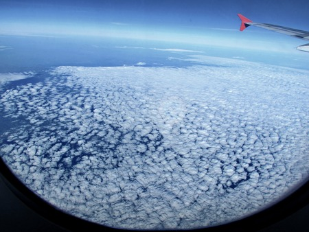 Take a Photo from plane of above the cloud in sky and wing of airplane.