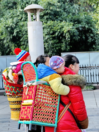 carried: Fenghuang ,December-28  2014, Lovely baby enjoy in basket carried by mothers at Phoenix Hall park in morning,Hunan,Chin