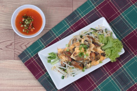 bean sprouts: Fried oyster with bean sprouts and shallot as Hoi Tod in Thai served with chili sauce. Stock Photo