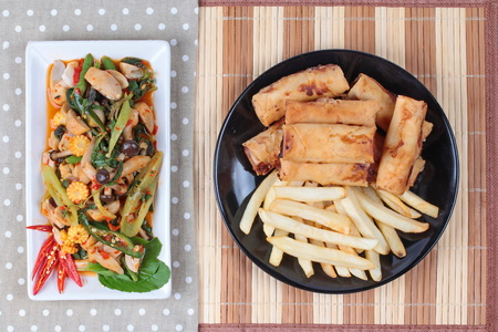 french roll: Chinese Vegetable festival  food as fried basil with mixed vegetables served deep fried spring roll and French fries .