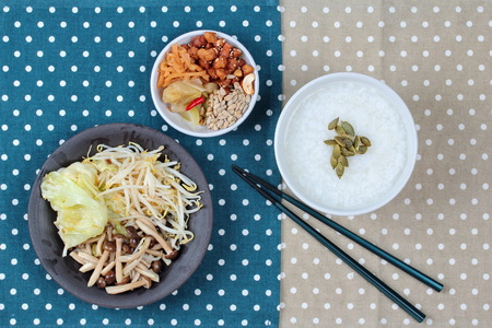 bean sprouts: Chinese vegetable festival as rice gruel and fried mixed vegetable served side dish.  (topped roasted pumpkin kernel and  fried mushroon, bean sprouts,cabbage served side disk as bean cabbage,sweet radish and pickle ) Stock Photo