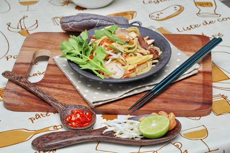 bean sprouts: Fried sour sweet  Chinese noodle with tofu,mushroom,red chili,bean sprouts, green lemon,lettuce with side dish as sliced red hot chili pepper ,halved green lemon, bean sprouts and cashew nuts are popular Asia food.