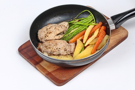 mixed vegetables: Home made ,Cooking pork steak with mixed vegetables in pan before served isolated on background. Stock Photo