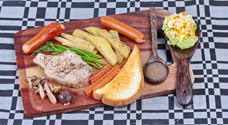 Pork steak and mixed vegetables on butcher served with side dish as parmesan cheese bread ,sausage ,shiitake fresh mushroom soup and salad,Home made.