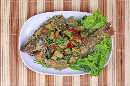 Green curry with  deep fried tilapia fish in coconut milk is popular Thai cuisine . Stock Photo