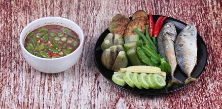 Spicy shrimp paste dip as  Nam Prik Kapi served with side dish as deep fired mackarels,boiled long-eggplant,lentils,winged bean ,red hot chili pepper and sliced cucumber. Stock Photo