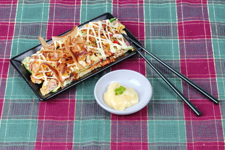Japan pizza as Okonomiyaki is fried mixed vegetable flour with meat topped sweet sauce ,mayonnaise or salad cream and sliced dried yellowfin tuna served with side dish.