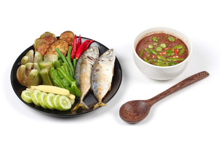 Thai local popular food as spicy shrimp paste dip , Nam Prik Kapi, is served with side dish as deep fired mackarels,boiled long-eggplant,lentils,winged bean ,red hot chili pepper and sliced cucumber. Stock Photo
