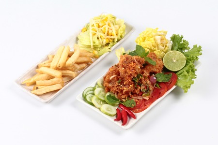 Spicy fried chicken salad (Yum Kai Zap in Thai) served mixed vegetales salad and french fires. Stock Photo