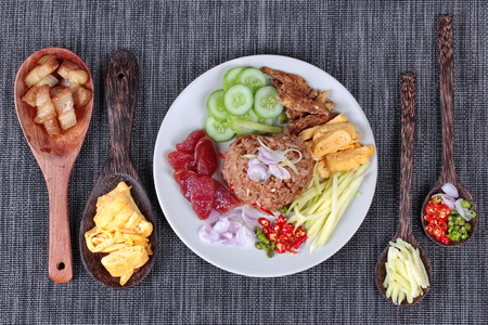 scrambled: Thai food ,Fried jasmine rice with shrimp paste,(Kao Klok Kapi) with green mango roll,Chinese sausage,crispy dried fish,shrimp,chili,shallots,stir sweet pork,cucumber and scrambled egg . Stock Photo