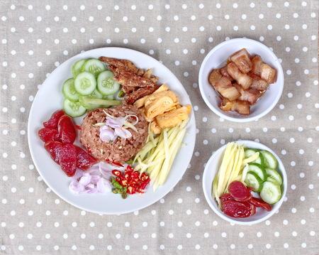 Thai food ,Fried jasmine rice with shrimp paste,(Kao Klok Kapi) with green mango roll,Chinese sausage,crispy dried fish,shrimp,chili,shallots,stir sweet pork,cucumber and scrambled egg . Stock Photo