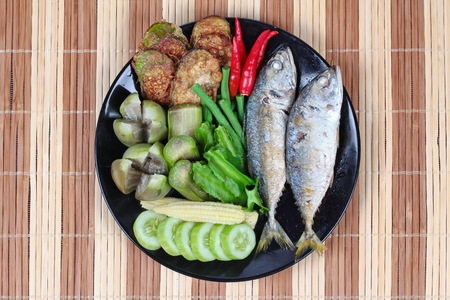 Ready side dish served  for Thai spicy sour dip   as deep fired mackarels,boiled long-eggplant,lentils,winged bean ,red hot chili pepper and sliced cucumber on wood.  Have text space for fillin. Stock Photo