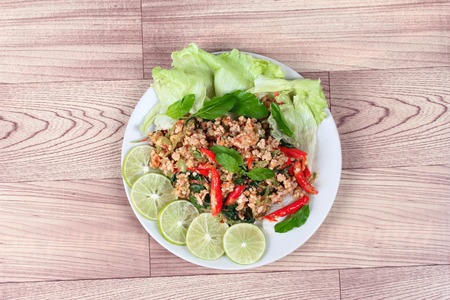 top ten: Fried spicy basil with minced pork topped sliced green lemon and and lettuce is top ten of popular Thai food.