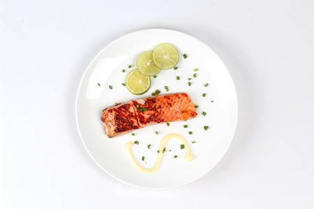 Grilled salmon topped minced shallot ,mayonnaise and sliced lemon on white dish. Isolated.