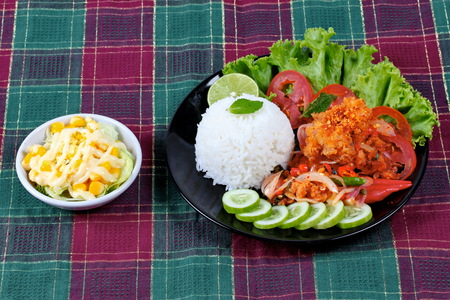 Home made,Jasmine rice with spicy fried chicken salad (Khao Yum Kai Zap in Thai) topped sliced cucumber,tomato,halved lemon and lettuce served with mixed vegetables salad.