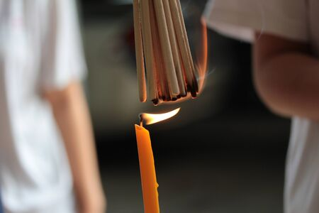 Chinese pay respect to ancestorst,Placing a lighted candle and lit for descendants using on good folkway. Selective focus. Stock Photo
