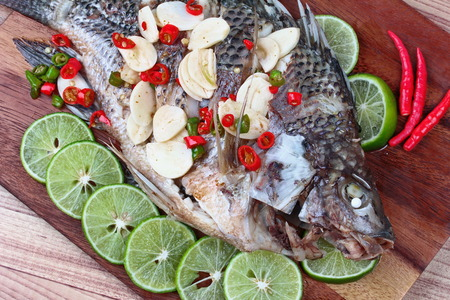 fishbone: Close up of a butcher served of Tilapia fish streamed with lemon topped spicy sour ginger and chili. (Call Pla Nil Nuang Manoaw in Thai) Stock Photo