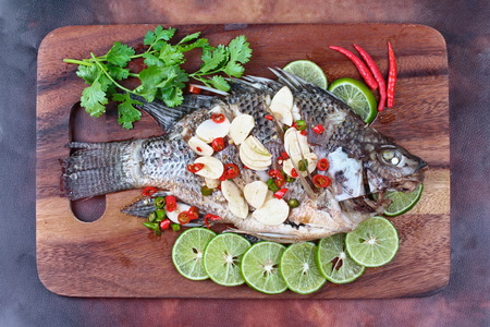 pla: Tilapia fish streamed with lemon topped spicy sour ginger and chili on butcher served. (Call Pla Nil Nuang Manoaw in Thai) Stock Photo