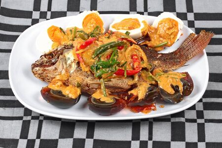 Curry-fried  tilapia fish with preserved egg and salted egg. Stock Photo