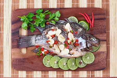 mined: Tilapia fish streamed with lemon topped spicy sour ginger and chili on butcher served. (Call Pla Nil Nuang Manoaw in Thai) Stock Photo