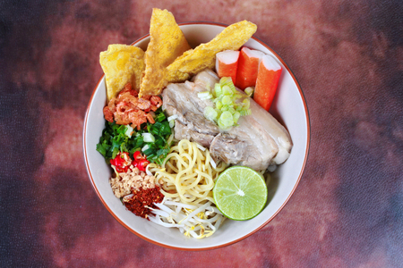 bean sprouts: Japanese noodle (ramen) in spicy sour soup as tom yam  topped  steamed streaky pork,wonton,chili ,green lemon ,crab stick,dried shrimp,minced roast nut ,bean sprouts and shallot in porks bone soup. Stock Photo
