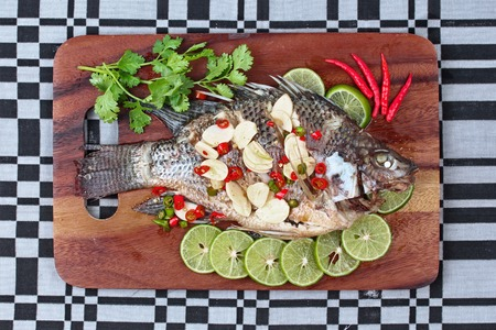 fishbone: Tilapia fish streamed with lemon topped spicy sour ginger and chili on butcher served. (Call Pla Nil Nuang Manoaw in Thai) Stock Photo