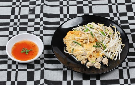 bean sprouts: Thai food,Fried egg and oyster with bean sprouts and shallot as Hoi Tod Khai in Thai served with chili sauce.
