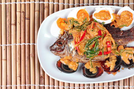 Curry-fried  tilapia fish with preserved egg and salted egg as topped a spicy curry with coconut milk.